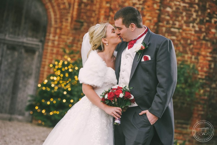 Bride & Groom Kissing in front of Leez Priory with fairy lights