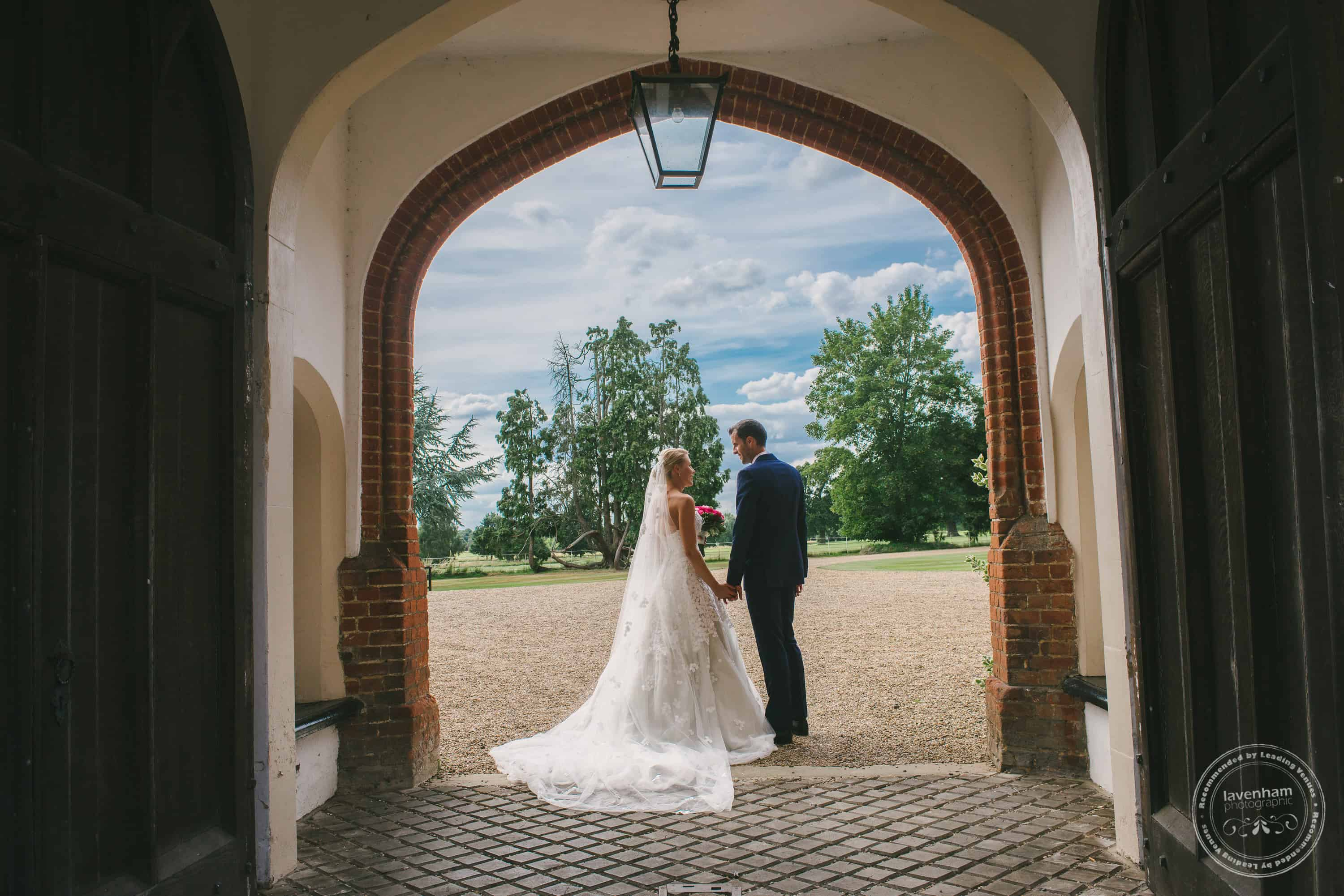 Blue sky framed by archway with bride and groom having a quiet moment