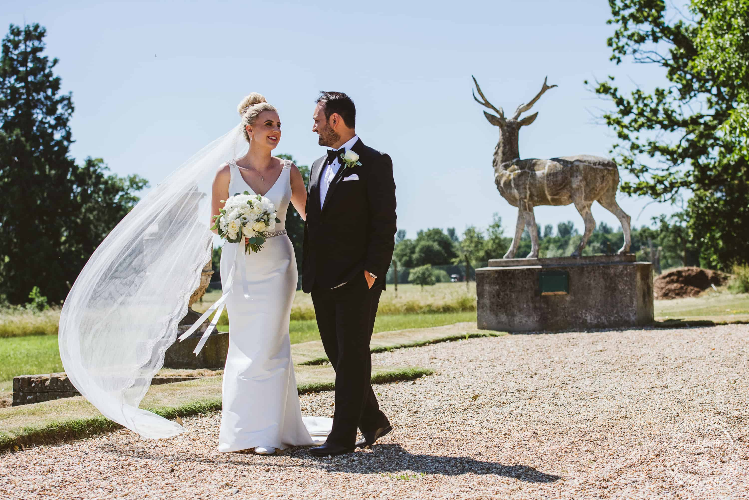Bride and Groom walking the grounds at Gosfield Hall, with stag statue behind. The bride's veil blowing gently in the wind.
