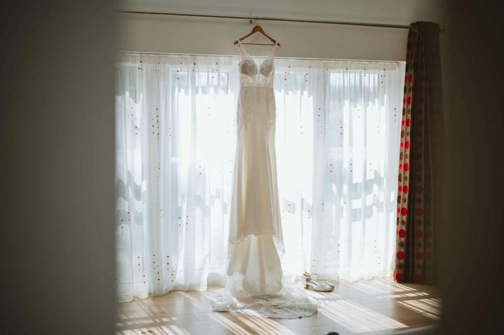 Wedding dress hanging in front of large windows