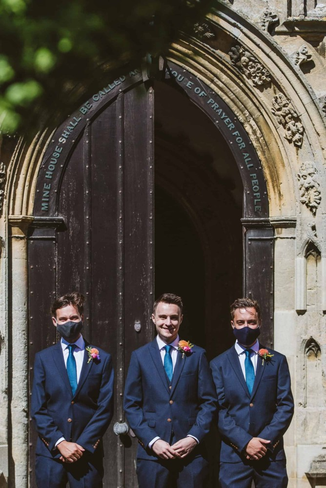 Groom with best man, wearing facemasks at wedding with covd-19 coronavirus restrictions
