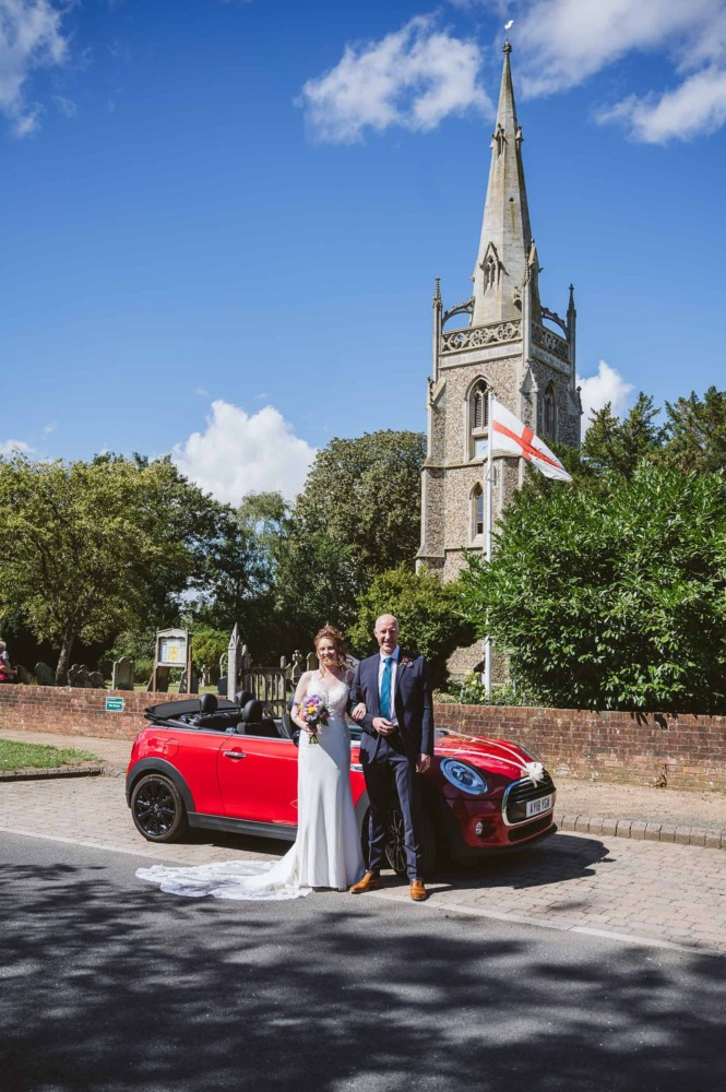 Bride arrives at church in a red convertable Mini