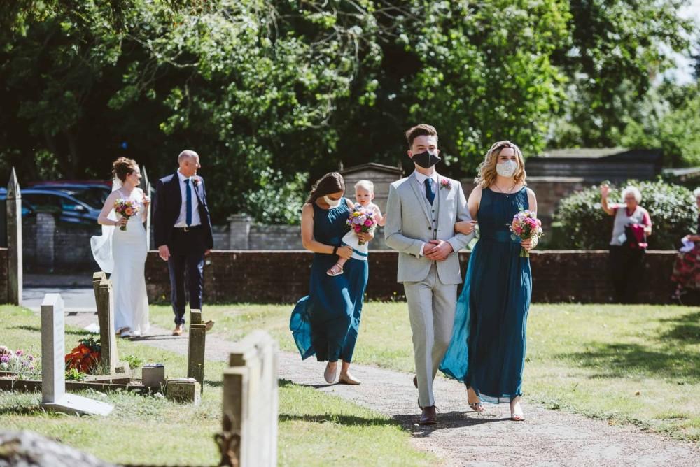Bridal party walk to church wearing coronavirus facemasks