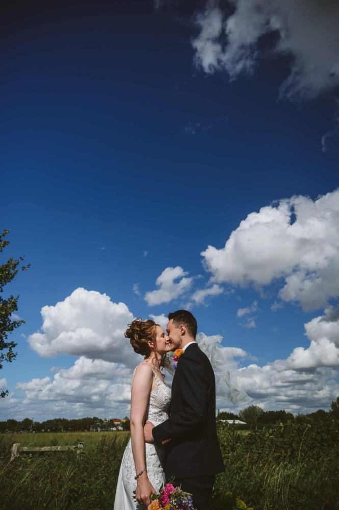 Big blue sky above the bride and groom in the Suffolk countryside