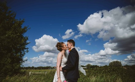 Bride & Groom kiss with blue sky behind