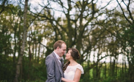 Bride and Groom embrace with woodland behind