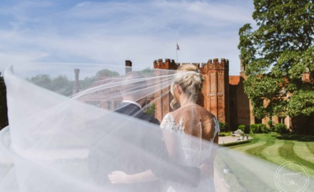 Bride and groom at Leez Priory on wedding day, with bride's veil blowing in the wind