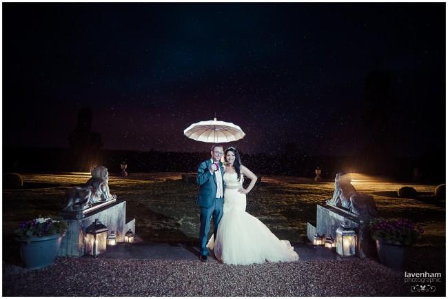 Bride and groom under umbrella in the rain at Gosfield Hall wedding, night portrait