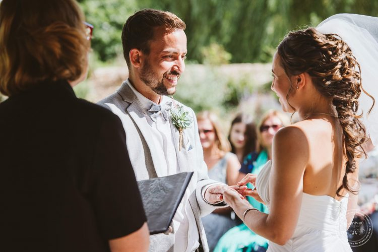 Bride and groom photographed exchanging vows during the wedding ceremony