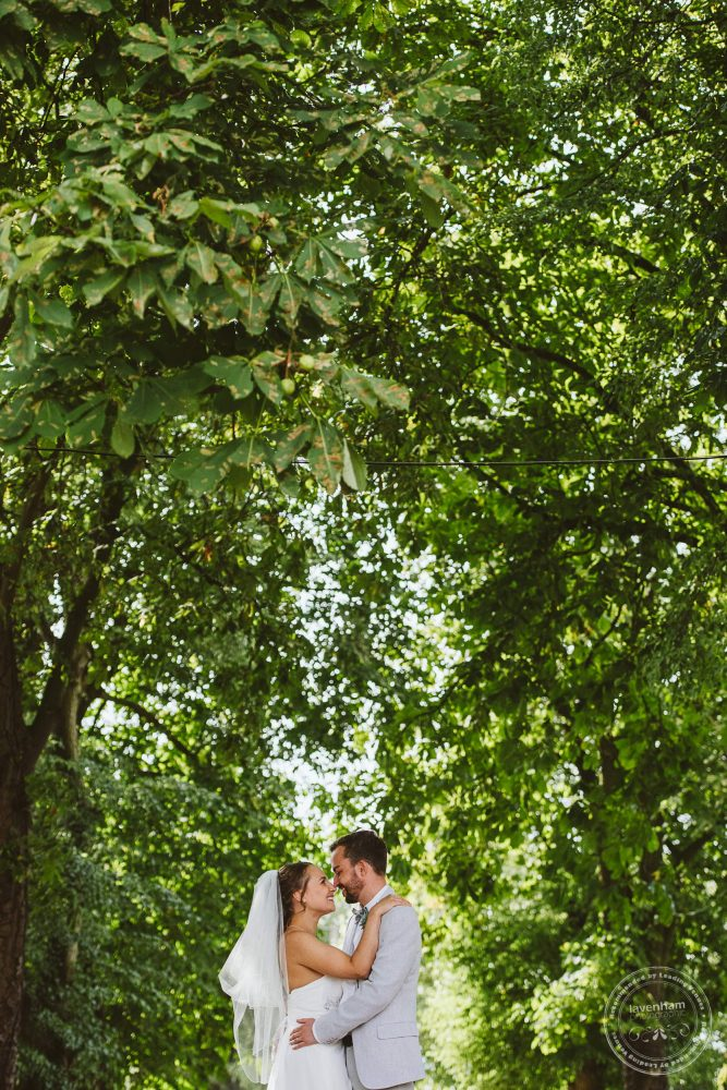 Bride and groom share a kiss among the trees
