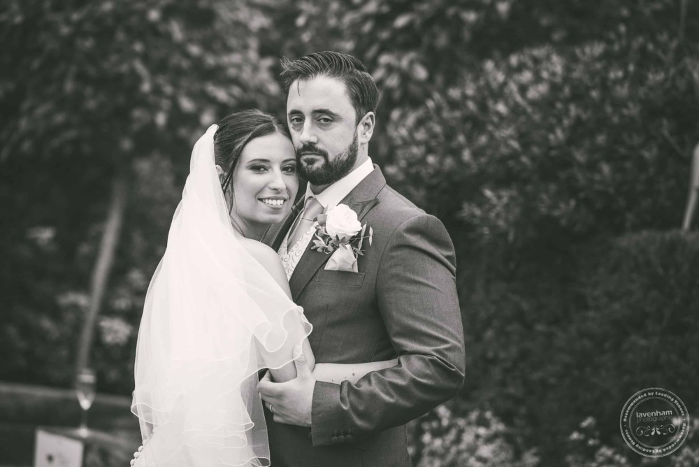 Black and white wedding photograph, bride and groom hold each other close with leafy background