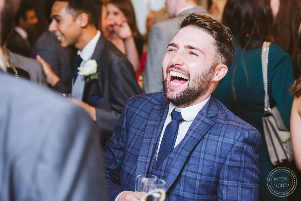 Wedding guests laugh and chat, during wedding reception