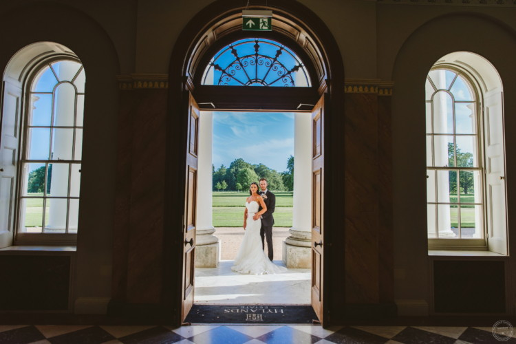 Bride and groom framed in Hylands House archway windows