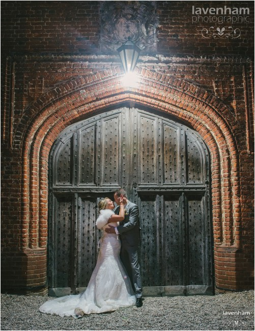 Night portrait of bride and groom at huge wooden doorway at Leez Priory, lit from lamp above