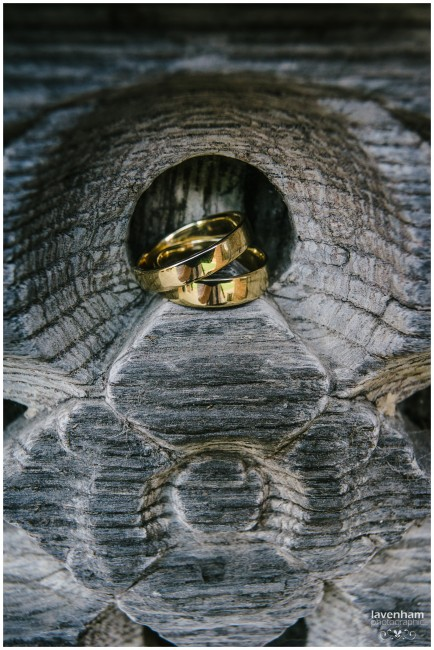 Detail of gold wedding rings on wooden carved detail