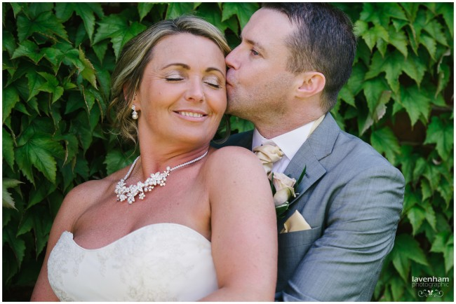 Bride and groom intimate moment photographed with leafy background