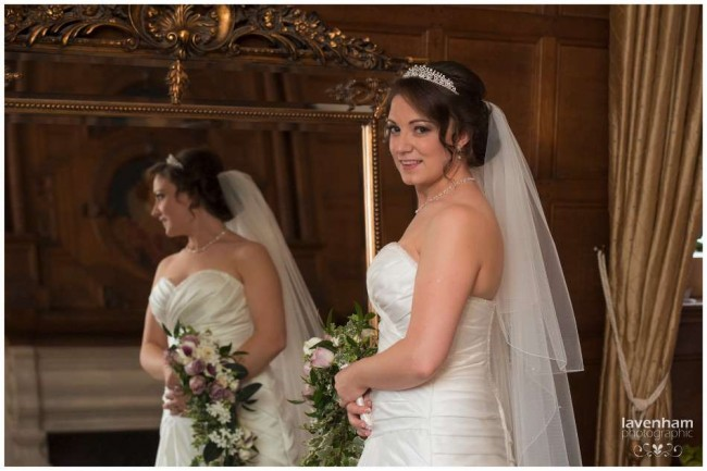 Portrait of the bride in front of large mirror in the bridal suite