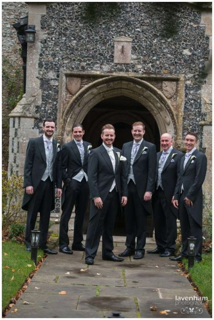 The groom with best man and ushers standing in front of the church