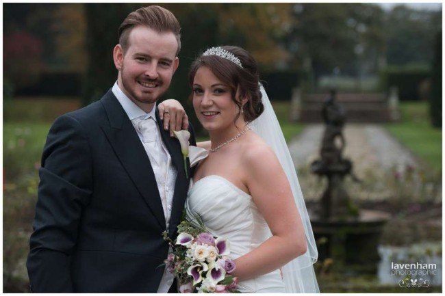 Posed photograph of bride and groom during wedding reception at hangrave hall, path behind