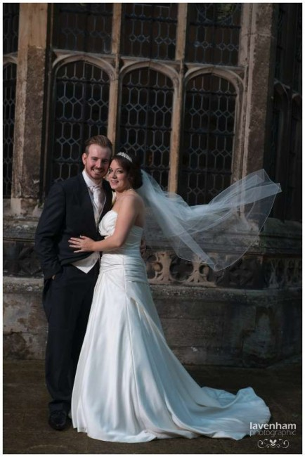 Bride and groom photographed with remote lighting, veil blowing in the wind