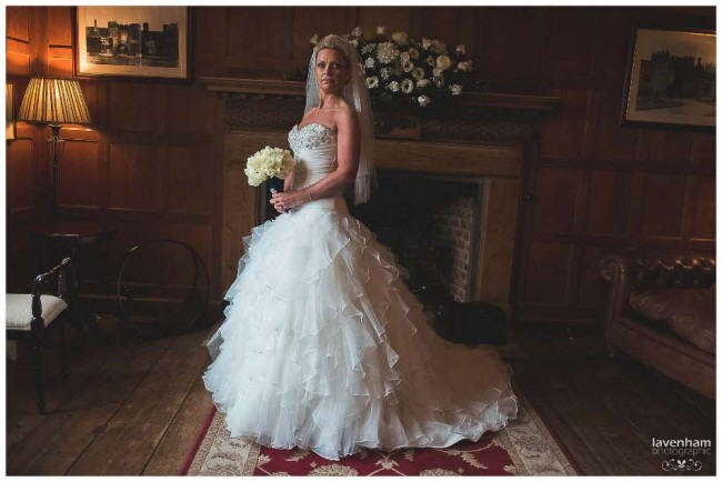 Full length portrait of the bride before the wedding ceremony in the Light Oak room at Leez Priory