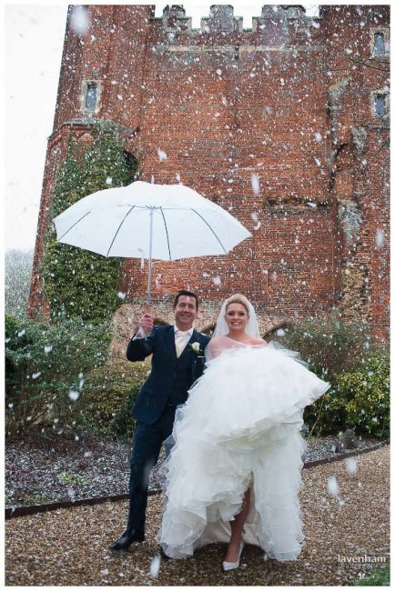 Bride and groom photographed walking back from the tower at Leez in the snow