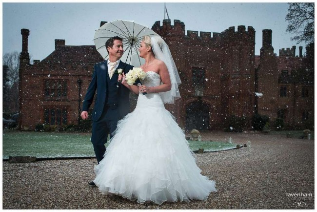 The Bride and groom photographed walking in the snow at Leez Priory, Essex