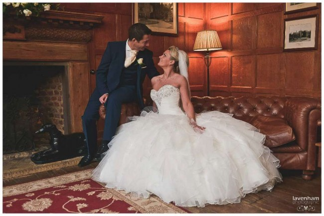 The Bride and groom on the sofa in the Light Oak Room at Leez Priory, showing the wedding dress