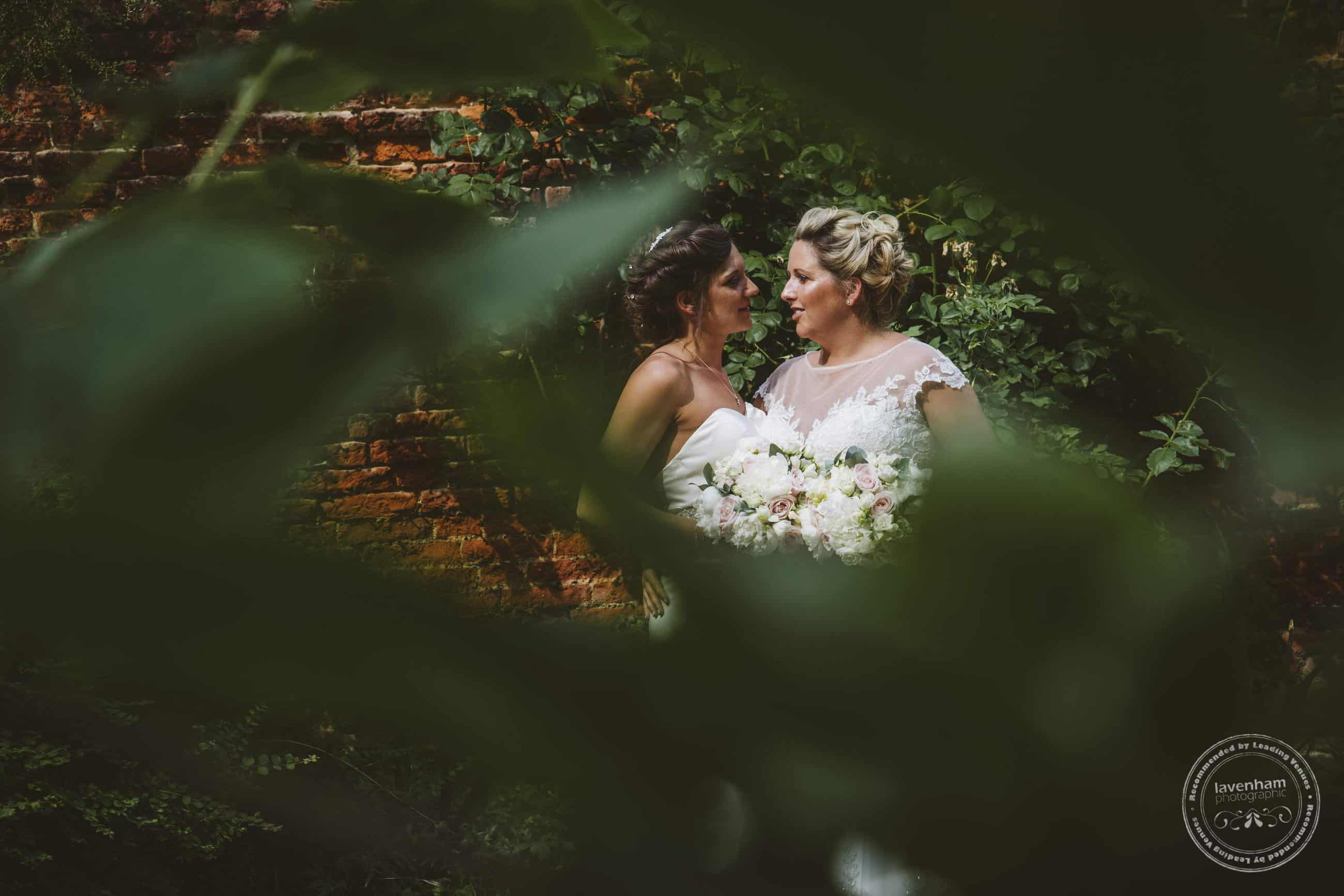 Framing a photograph through leafy foliage during a romantic photoshoot gives a more candid feel