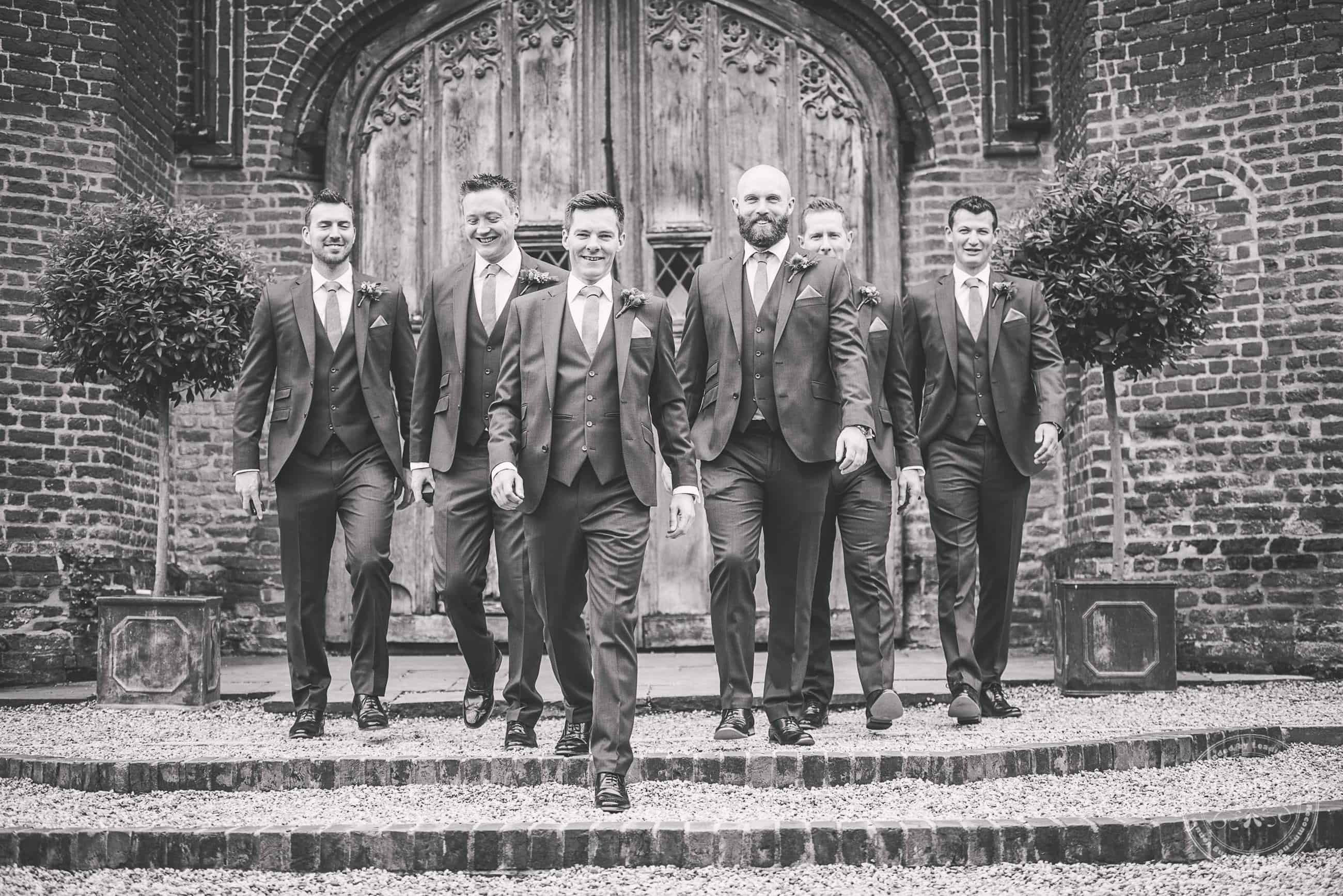 Groomsmen walking with a carved wooden doorway at Leez