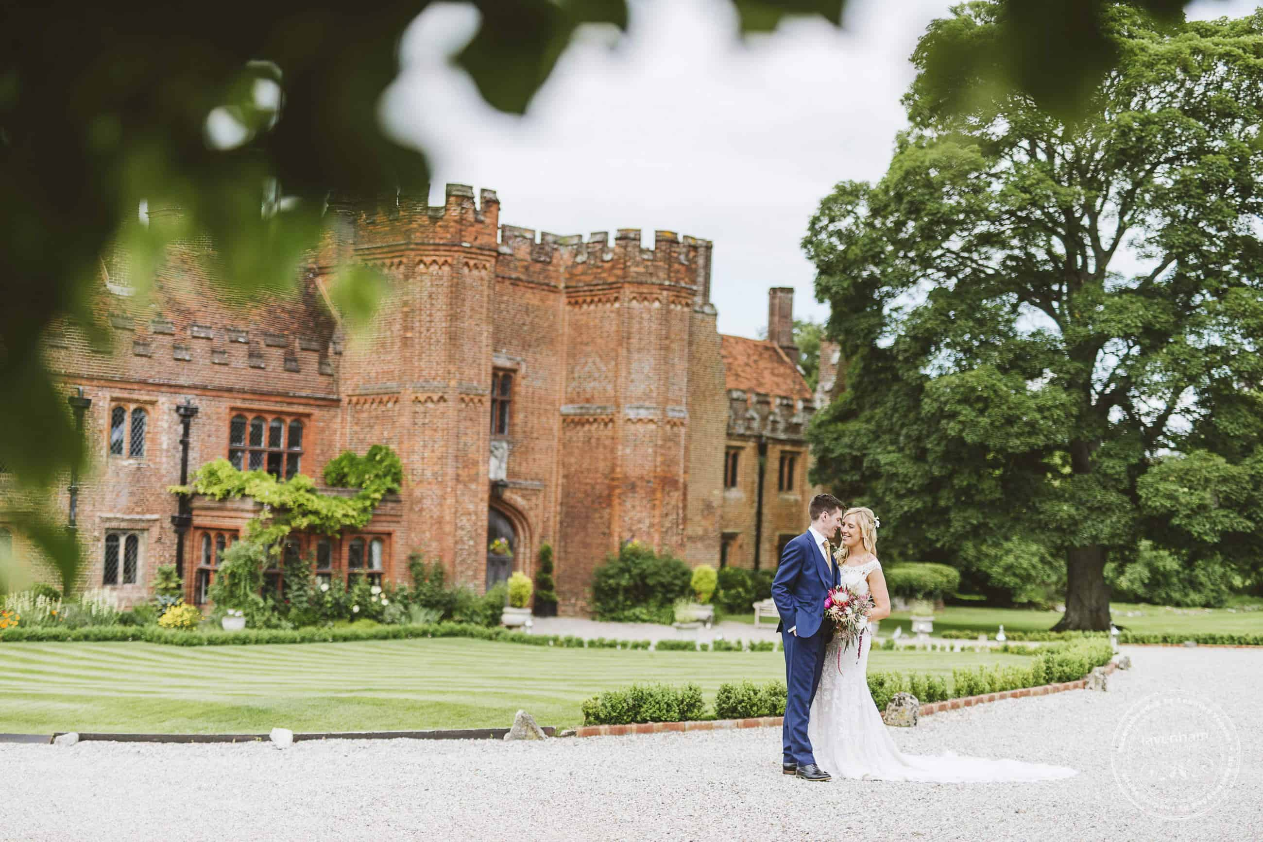 Leez priory wedding photo, framed through leafy trees