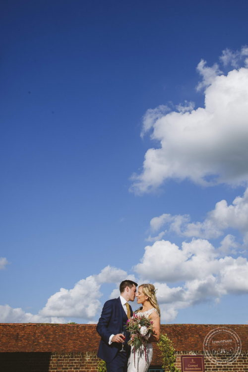 Wedding photo with blue sky and fluffy clouds
