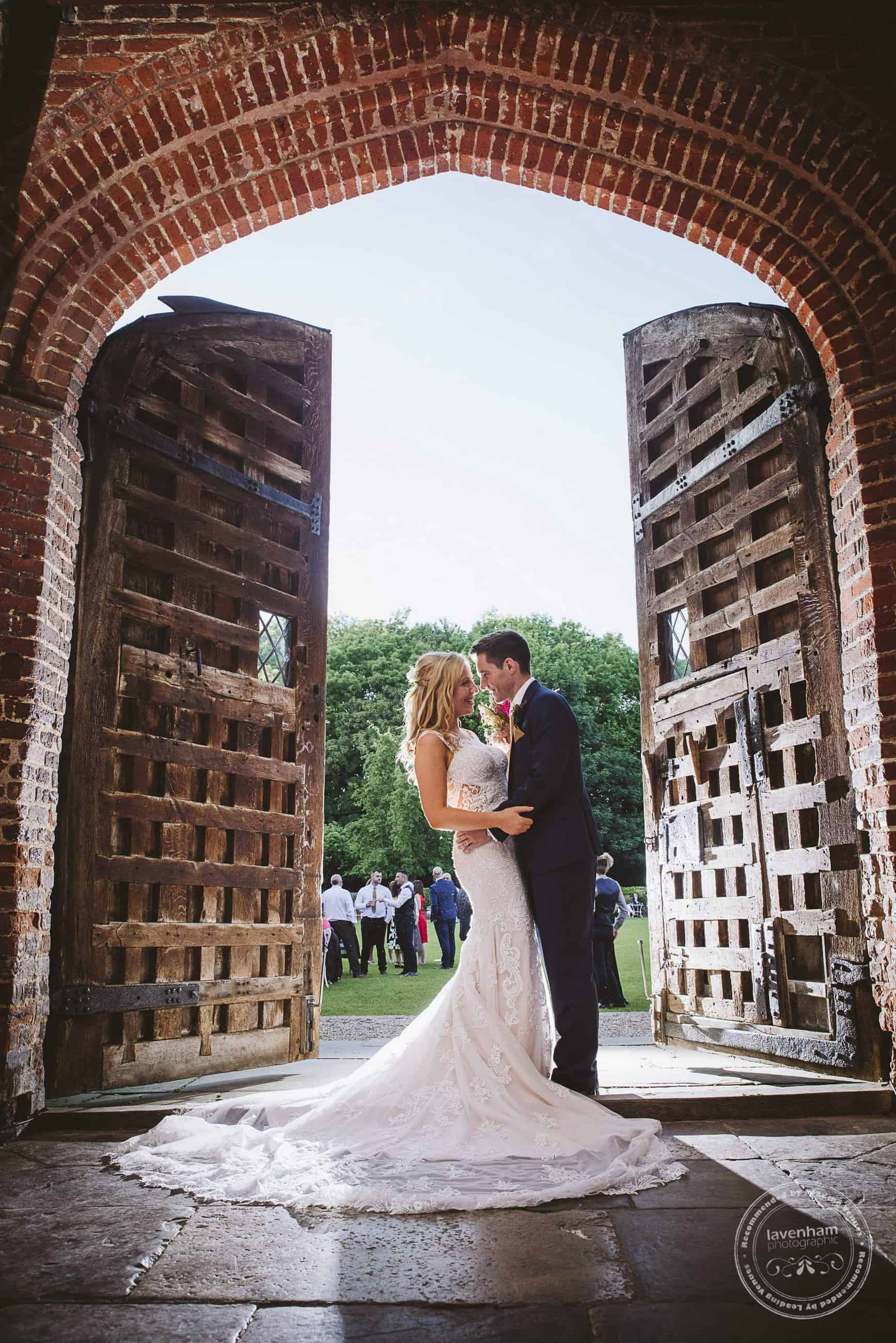 Bride and groom stand between huse carved wood doors