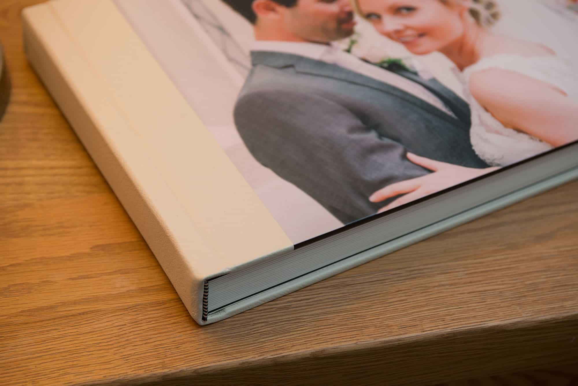 Close up of a wedding album with photographic cover and cream leather spine