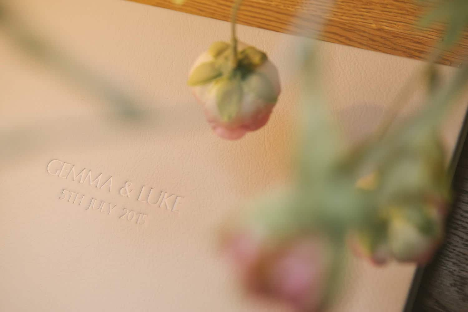 Close up of the embossed words on a cream leather wedding album cover
