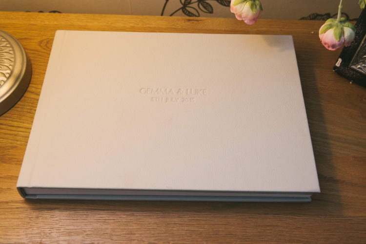 Cream leather wedding album with embossed text on the cover