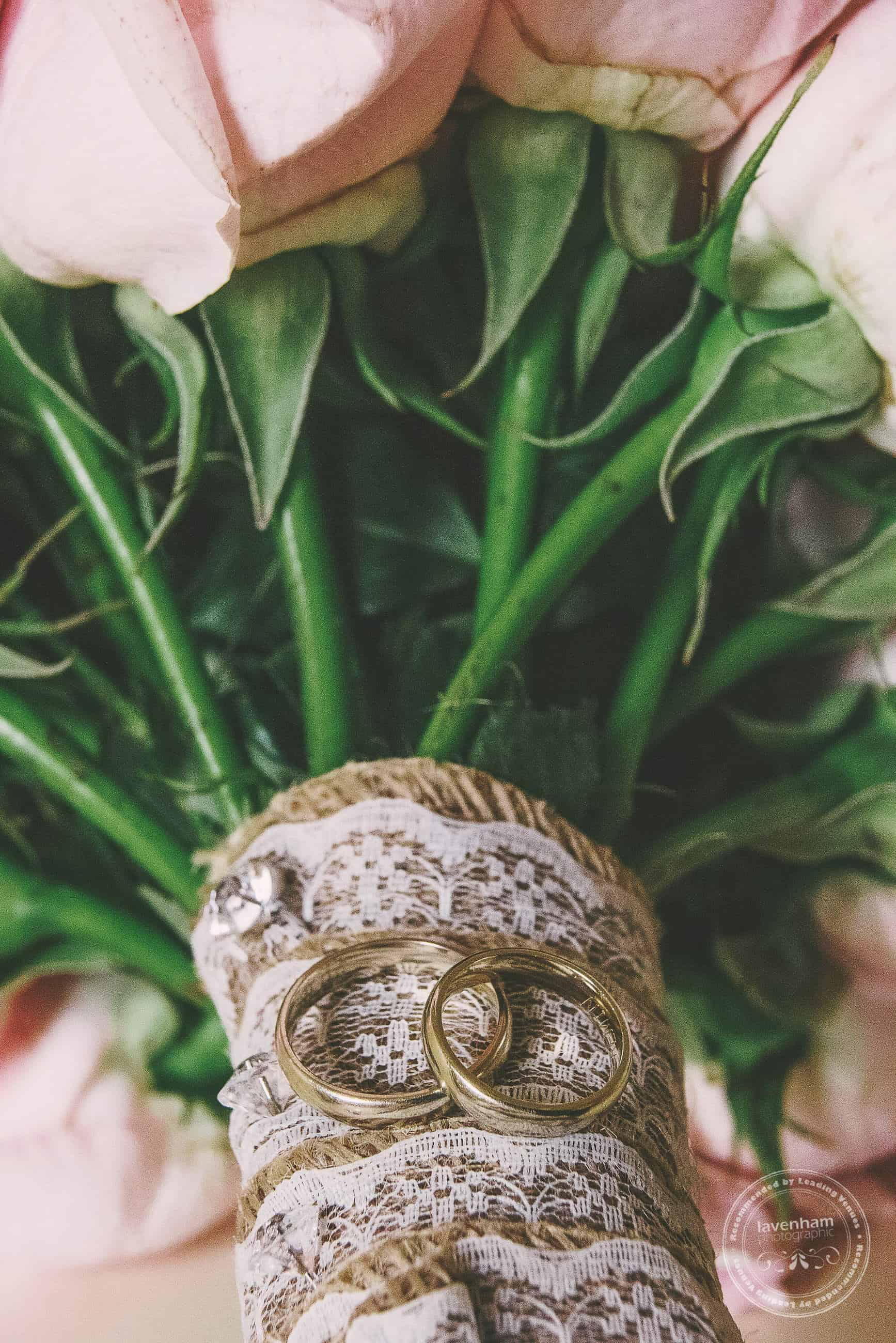 Wedding ring detail photo, sitting on hessian and lace detailing of bouquet