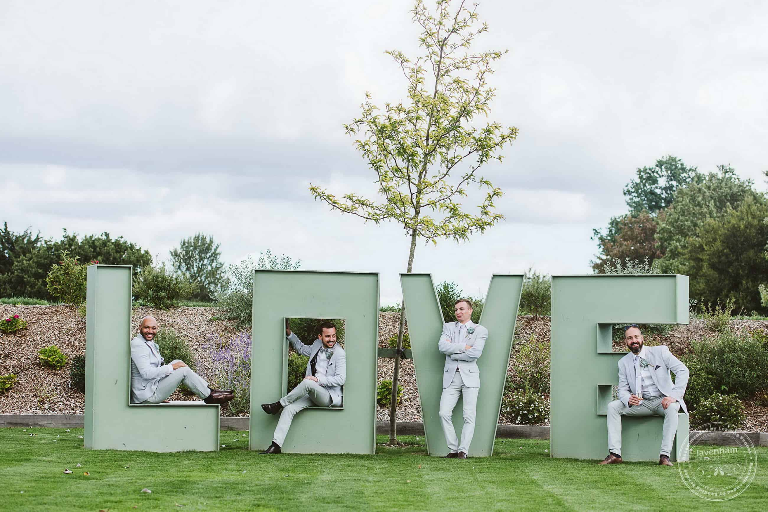 Groomsmen sit within the LOVE marquee letters in the ground at the Channels estate
