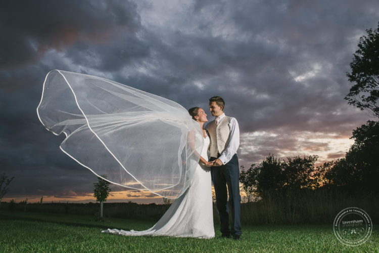 Dramatic evening sunset photo with bride's veil flying in the wind. This shot was created with the help of an off-camera flash, balanced carefully to show the sunset and light the bride and groom well.