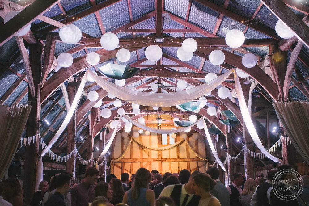 Guests mingling at Alpheton Hall Barn, details of drapes and balloons in the rafters of the barn