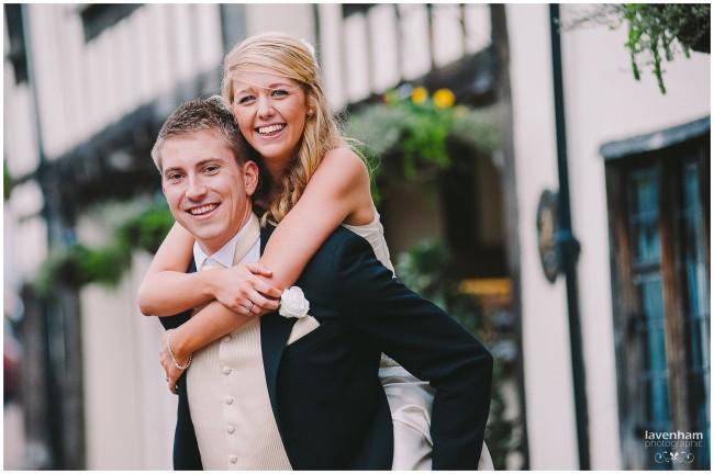 Fun wedding photography - bride piggyback on groom's shoulders at The Swan at Lavenham
